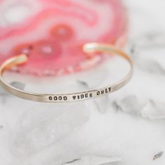 """These dainty stack-able bracelets are a subtle way to add some inspiration to your day. This brass cuff reads, """"good vibes only"""", because who doesn't need that reminder?  As with all of our pieces this brass quote bracelet is made with great care, each letter and symbol is hand stamped and polished by hand."""
