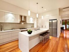 ♥ jmk says:- Love the contrast between the high gloss white units and the warm wood floor: