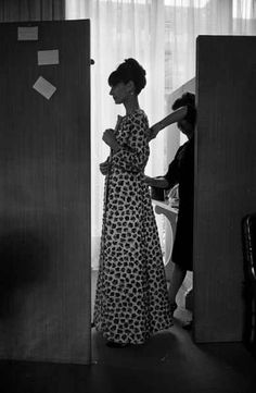 The actress Audrey Hepburn photographed by Roger Viollet at the Maison Yves Saint Laurent, while the seamstress did some adjustments in this long dress (made of silk, chemisier style), commissioned by Audrey of the haute couture collection for Spring/Summer of 1964. Paris (France), April 1964.