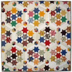 Galaxy quilt is a variation on the traditional seven sister block using sashing and tumbling block posts.