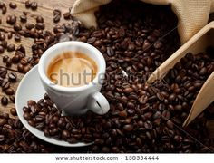 Espresso, coffee cup with smoke and coffee beans on wooden table. by Antonio Gravante, via Shutterstock