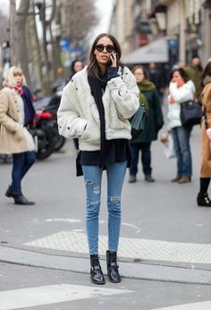 A luxe furry jacket with a sweater, jeans, and combat boots.