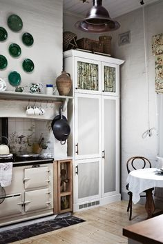cocina de estilo rústico, cocina de leña en el hueco de la antigua chimenea, armario restaurado, paredes de ladrillo visto pintadas de blanco, suelo de parquet