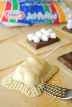 DIY S'mores Pie Pops with Hershey's chocolate, marshmallows and pie crust on a stick.
