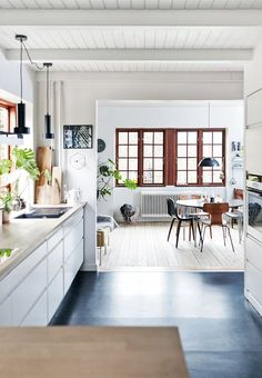 Bright open kitchen with a cool black linoleum floor, white kitchen elements and a massive wooden countertop. The open space with dining area creates a feeling of one huge room.
