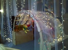 love the sheer fabric and twinkle light idea!