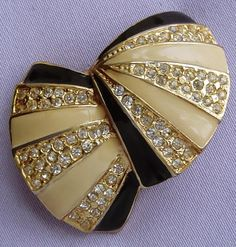 This fabulous, quality Art Deco brooch has a lovely double shell design. Made from base metal with a mink & black enamel & goldtone finish, it is adorned with shimmering faceted diamante stones.