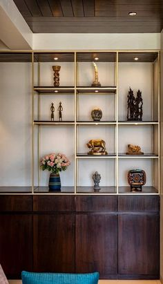 Linear Wooden ✨ Storage Cabinet with Wooden Shelves & Metal Dividers for placing Décor Elements & Antiques highlighted with Spot ✨ Lights - GharPedia Spot Lights, Storage Units, Pooja Rooms, Wooden Shelves, Cabinet Design, Dividers, Living Room Interior, Living Room Designs, House Design