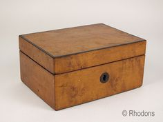 Antique Wooden Box believed to date to the Victorian era - circa 1880's. Compact box in a honey coloured wood (possibly yew wood), with ebonised stringing to the hinged lid. The lid having an internal mirror,  Brass hinges and lock (no key present). Later green baize fabric lining with a pink coloured cording around the mirror.