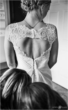 Bride gets help with her gown with an open back at Lower Lake Ranch in Pine, Colorado