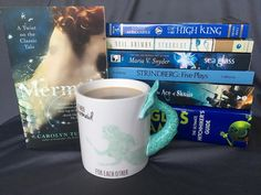 Look at my new coffee mug!!!  I have approximately zero mermaid themed things so I decided that needed to change.  The only thing I don't like is that it's one of those fussy ones that can't go into the microwave and I take ages to drink my coffee. . . Also doing the #shadesofblue tag from @juliablakeauthor and a few other lovelies. . . . #booknerd #books #booksarelife #booksaremagic #bookstagram #bookstagramcommunity #bookstagrammer #bookworm #read #reader #reading #mermaid #bluebooks