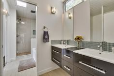 Mid-Century Modern Remodel by Four Seasons Properties. The second bathroom pocket door separates the custom porcelain tile shower and bath tub from the floating double vanity and toilet making it a useable hallway bathroom with tons of extra space.