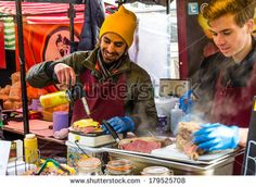 LONDON, UK - 1ST MARCH 2014: A man melting cheese using a blow torch at a stall in Camden Food Market - stock photo