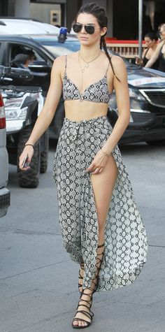 Kendall Jenner brought her vacation style to the next level and turned swimwear into street wear with a python-print bikini top and matching split pants, both by Zimmermann, that she styled with layered necklaces, aviators, and black lace-up flat sandals.
