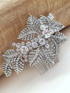 """Hallie Antique Floral Bridal Comb is a timeless treasure. This exceptional bridal comb is an alluring combination of rhinestone encrusted leaves and bold sparkling crystals. This bridal comb is intricately textured and designed and can be worn with a variety of hair styles. This headpiece secures to the hair with a 2"""" comb at the"""