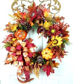 """Handmade Fall Pumpkin Sunflower Door Wreath - Autumn Sunflower Pumpkin Wreath, Harvest Sunflower Pinecone Wreath - Fall Grapevine. Delightfully colorful and full of many textures, this Fall Autumn wreath will grace any door with pumpkins, sunflowers, pine cones, and a triple ribbon bow. The base of this wreath is a 16"""" grapevine wreath. Beautiful fall Maple leaves encircle the entire wreath. Springs of berries and yellow and orange cypress poke out from behind the foliage. Various green..."""