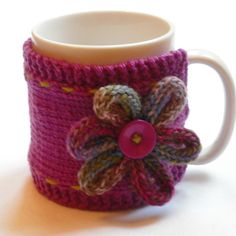· Handknitted mug hug, comes with the white mug. Knitted in margenta merino wool, decorated with green stitching and a wool loopy flower. Please contact me if you would like it in another colour as i do… Mug Rug Patterns, Easy Crochet Patterns, Crochet Designs, Knitting Patterns, Crochet Mug Cozy, Crochet Gifts, Crochet Basket Tutorial, Mug Rugs, Christmas Mugs