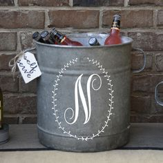This tall galvanized bucket is stunning with its laurel monogram design! Add this vintage piece to your home for charming rustic decor with a personalized touch.