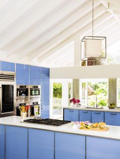 Boasting a soaring, exposed ceiling, Wedgwood blue tempered glass cabinets, quartz countertops and pro-grade appliances, this Florida kitchenis a chef's dream. A high-end choice, the glass cabinets are not only easy on the eyes, they're also a snap to keep clean.