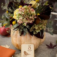Autumnal Pumpkin CenterpiecesThese beautiful pumpkin centerpieces were a long time in the making. Months before the wedding, Caitlin and Mark selected several varieties of pumpkins and had them grown by the Boujikian Farm in Torrance, CA. The day before the wedding the couple and their families hollowed out the pumpkins and filled them with beautiful arrangements of hydrangeas, billy ball, roses and eucalyptus berries made by florist Brianne Arrista.