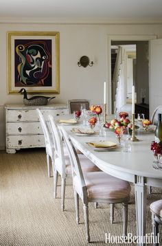 Dining room in a beautiful Cape Cod home by Kathryn M. Ireland. A sea-grass rug covers the floor. Ireland reupholstered the owners' Gustavian chairs and had the matching table made by the Lief gallery.  JAMES MERRELL