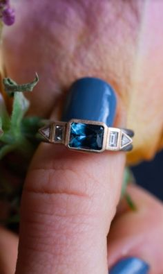 An east west emerald cut sapphire ring that blends boho style with modern geometrics design. The Christina is a truly unique custom engagement ring that takes the road less traveled at almost every turn. An emerald cut teal sapphire is bezel set horizontally and flanked by diamond baguettes and and triangle diamond accents. This east west emerald cut sapphire ring was designed and named for an Abby Sparks Jewelry client. #bohowedding #bluesapphirejewelry #custommade #mixedmetaljewelry…