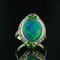 A gorgeous, thick cabochon black opal displaying a palette of blues and greens with flashes of orange is encircled by a strand of tiny freshwater seed pearls and accented with striking green and black enamel. A dramatic and wonderful example of American Art Nouveau circa 1900.