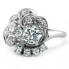 The Valerian Ring from Brilliant Earth  This incredibly distinctive Retro ring features a round brilliant diamond at the center, completely surrounded by accent diamonds in a variety of settings. One side boasts a row of four round brilliant diamonds, while others glimmer with diamond panels and luxurious milgrain swirls (1.11 ct.tw.).