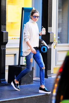 Olivia Palermo wears a turtleneck sweater, distressed skinny jeans, platform slip-on sneakers, mirrored sunglasses, and a black satchel