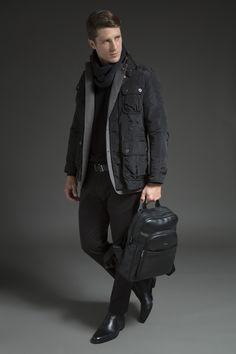 Tricô preto sobreposto por blazer cinza de algodão em padrão espinha de peixe, rain jacket com bolsos utilitários (referência militar) e cachecol de lã. A calça chino, o cinto, a chelsea boot e a mochila de couro finalizam o look all black sofisticado, ideal para os dias de frio e chuva.