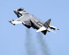 an AV-8B Harrier II takes off almost vertically, seen from behind and left. Picture by Daniel J. McLain, USN,