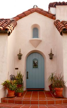 White stucco, red tile roof, and blue painted arched door on a Spanish Revival style house.