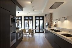 black brown kitchen white walls black doors wooden floor - LIKE