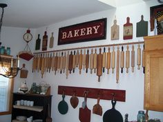 Kitchen going back to prim.I made the bakery sign from an old door.Love those rolling pins!