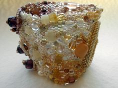 Peyote cuff bracelet with pink jasper cabochon, carved and dyed tagua nuts, pearls, Czech and Indian glass, Japanese seed beads all blend together in a desert sunrise color palette. Glass crow beads are used as the button-type closure.