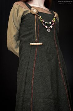 Rekonstruktion eines Trägerrockes. Charakteristisch sind der taillierte Schnitt sowie die leicht nach vorne versetzten seitlichen Nähte (vgl. Inga Hägg - Die Textilfunde aus dem Hafen von Haithabu. Berichte über die Ausgrabungen in Haithabu Band 20). Unterkleid aus Leinen mit Wollbesatz.