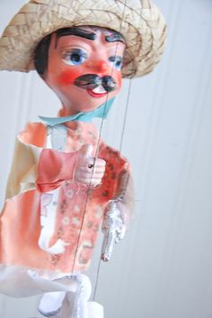 This vintage Mexican marionette puppet is on strings. He looks like Poncho Villa. He has a charming face with big mustache, nice hat and handsome fabric outfit with peach and blue. His hands are carry