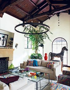The wood panel ceiling of the couple's living room marks the space with a warm, inviting aesthetic. A large horse sculpture made of old car parts gives the arched window commanding grandeur, while the oversized mirror above the fireplace creates a similar dramatic effect. The room is marked with personality-driven vintage pieces, such as trinket boxes, and a central hanging pendant.