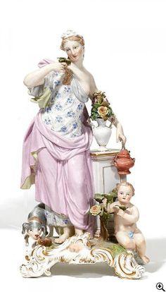 Allegorie 'Der Geruch'  19.Jh. Modell J.F. Eberlein, 1745. Porzellan, farbig und gold staffiert. Aus der Serie 'Die fünf Sinne'. Allegorie in antikem Gewand mit Blumen und Weihrauchgefäß. Begleitet von Putto und Hund. Rocaillesockel mit symbolischer Nase. Höhe 27,5 cm. Schwertemarke, 1051, Malernummer 13. Zustand C.