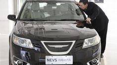 Chairman Jiang Dalong kissing a new Nevs 9-3 Corporate Sedan (2016) electric car, prototype, as he poses during an interview at its Beijing.