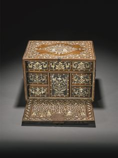 A Mughal ivory-inlaid wood fall-front cabinet with figures. Gujarat or Sind, 17th century, composed of two tones wood with ivory inlay, top and front featuring a couple beneath a tree in a lobed medallion, sides and reverse with foliate stylised design, brass handles for carrying, interior of hinged lid with two couples in a forest with birds, with eight compartments opening to reveal six drawers Old Boxes, Antique Boxes, Antique Metal, Indian Furniture, Antique Furniture, Ottoman Furniture, Homemade Home Decor, Antique Collectors, Wooden Storage Boxes
