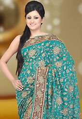 Look stunning rich with dark shades and floral patterns. This lturquoise faux georgette saree have beautiful embroidery patch work which is embellished with zari and sequins work. This saree gives you a modern and different look in fabulous style. Matching blouse is available. Slight Color variations are possible due to differing screen and photograph resolutions.