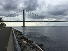 A school of fish jump on a cloudy day on the Narrows. The horizon, past the Verrazano Narrows Bridge, is clear in the distance - September 22, 2015 - Photo by James Scully