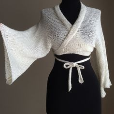 """Ivory Ballet Wrap Sweater Knit Half Kimono $50 Loose holey knit sheer ballet wrap crop sweater. Cross over shrug reminiscent of kimono with its hem collar and wide 3/4 length sleeves. Long ties that you can tie loosely in front for a cardigan look, wrapped over and tied in back, or wrapped and tied in front if you have a 26"""" or smaller waist. Falls just to under bust. Mannequin is 32-24-34. Made of 98% rayon 2% nylon, a soft light fuzzy bouclé [discontinued] yarn. Hand wash, light steam…"""