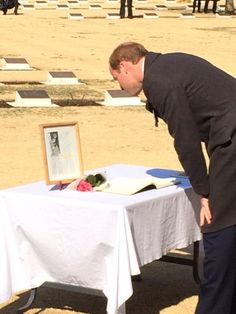 Prince William, Duke of Cambridge looks at a photograph of his mother, Diana, Princess of Wales.