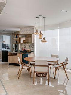 Decoração de apartamento aconchegante e atemporal com mesa de madeira redonda, cadeira de madeira estofada e plantas.