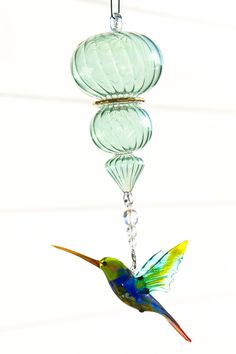 Green Headed Glass Hummingbird with Handblown Green Spiral Suncatcher Ornament. This handmade glass lampwork Green Headed Hummingbird is a great addition to any home window or indoor bird house. Simply hang anywhere and enjoy the sparkles! Comes beaded with crystal and a Spiral Handblown Glass Ornament. the total length is 10 inches with the Hummingbird being 4 inches wide by 2.5 inches long. This is a great gift for anyone who loves their garden and/or loves looking at hummingbirds…