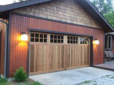 Wooden #garagedoor, giving a carriage house style look and the lighting lamps…