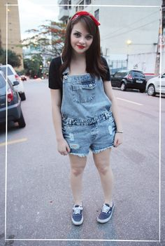 Jardineira jeans maravilinda com Vans e lacinho no cabelo.