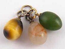 Three Russian miniature egg pendants, one nephrite on a 14 carat gold (56) ring, one tiger's eye on a silver (84) ring, and one chalcedony on a white metal ring. Each approx. 2cm, circa 1900. Provenance: property of an emigre who left Russia circa 1917.